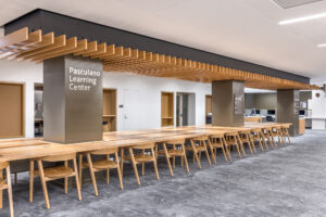 Photo of a long wooden table in the Pasculano Learning Center inside of the Stavros Niarchos Foundation Library (SNFL)